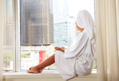 Pretty female sitting by a window Royalty Free Stock Photography
