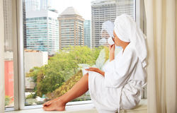Pretty female sitting by a window Stock Photography