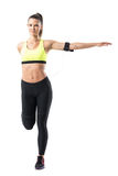 Pretty female sporty jogger stretching leg and arm balance exercise stock image