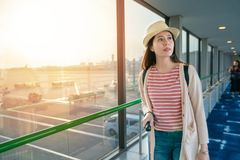 Pretty female standing next to large windows. View in airport japan royalty free stock image