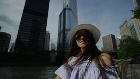 Pretty female is standing on the quay with her hair waving in the wind. stock video footage