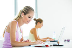 Pretty, female student with books and laptop Stock Images