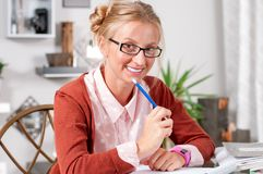 Pretty female student with books working in a high school royalty free stock images