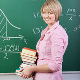 Pretty female student carrying books in class Stock Image