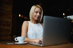 Pretty female student with cute face keyboarding something on net-book while relaxing after lectures in University Stock Photography