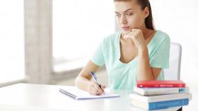 Pretty female student doing homework stock video footage