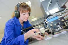 Pretty female student doing practical work at factory royalty free stock image