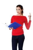 Pretty female student holding notebook pointing up Royalty Free Stock Photo