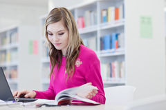 Pretty, female student with laptop and books Royalty Free Stock Images