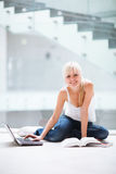 Pretty female student with laptop and books Stock Image