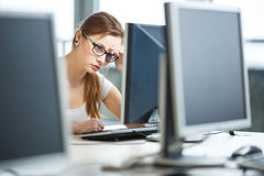 Pretty, female student looking at a desktop computer screen Royalty Free Stock Photo