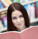 Pretty female student looks through the book Stock Photos