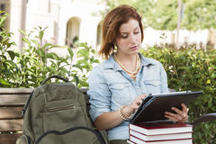 Pretty Female Student Outside on Bench Using Touch Tablet Royalty Free Stock Images