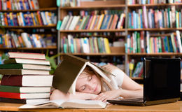 Pretty female student sleep in library Stock Photos