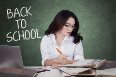 Pretty female student studying with books in class Royalty Free Stock Image