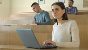 Female student study on laptop. Pretty female student studying on laptop at the college. Attractive brunette girl looking at the laptop screen. Young caucasian Royalty Free Stock Photography