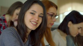 Female student turns her face at the lecture hall. Pretty female student turning her face to the camera at the lecture hall. e view of young undergraduates Stock Images