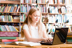 Pretty female student typing on notebook in library Stock Photos