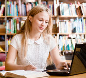 Pretty female student typing on notebook in library Royalty Free Stock Photos