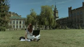 Pretty female student working on laptop on lawn. Attractive long brown hair female college student working on laptop pc and making notes in notepad while sitting stock footage