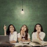 Pretty female students thinking idea. Three pretty female high school students studying together and thinking idea under a bright light bulb Stock Photography