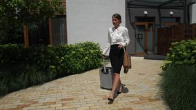 Pretty female with suitcase going on business trip