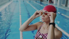 Pretty female swimmer putting on her goggles on her face for underwater floating, She wear swimsuit and red swim cap. Focused woman ready to training in stock footage