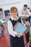 Pretty female teacher posing in her classroom holding some files Stock Photo
