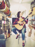 Pretty female teenager examining various acoustic guitars. In guitar shop Stock Photos