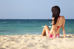 Pretty female teenager looking at sea on the beach. Pretty young woman with bikini looking at ocean on tropical beach Royalty Free Stock Image