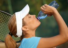 Pretty female tennis player drinking water Royalty Free Stock Images