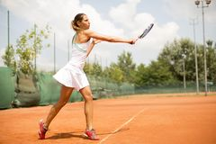 Pretty female tennis player playing on court Royalty Free Stock Images