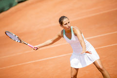 Pretty female tennis player playing on court Stock Images
