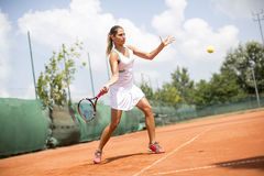 Pretty female tennis player playing on court stock photo