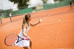 Pretty female tennis player playing on court on a sunny day royalty free stock photo