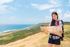 Pretty female tourist holding map guide reading. Hiking route content standing on hill mountain top with ocean background stock photography