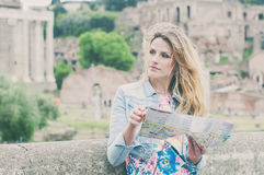 Pretty female tourist looking a map on the ruins of the Roman Fo Royalty Free Stock Images