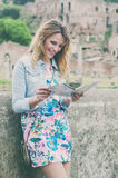 Pretty female tourist looking a map on the ruins of the Roman Fo Royalty Free Stock Photography