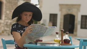 Pretty female tourist sitting in cafe with map in hands, examining journey route. Stock footage stock video