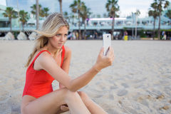 Pretty female tourist in swimsuit taking picture with her smart phone while sitting on the beach Royalty Free Stock Images