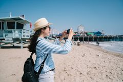 A pretty female tourist taking picture of beach stock images