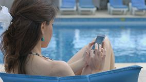 Pretty female typing message, texting on smartphone near pool. Stock footage stock video