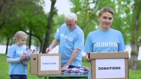 Pretty female volunteer holding box, activists sorting clothes on background stock video footage
