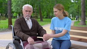 Pretty female volunteer supporting aged male patient in wheelchair, assistance. Stock footage stock footage