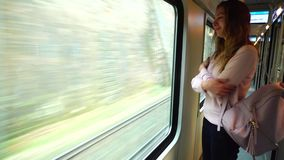 Pretty female voyager leaves city and stands in  train near large transport window. Alluring girl rides on  train and remembers  pleasant moments of  journey stock footage