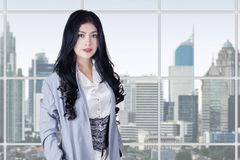 Pretty female worker with long hair in office Stock Photo