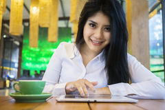 Pretty female worker using tablet in cafe Stock Image