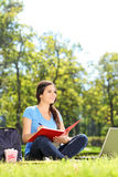 Pretty female writing in a notebook outdoors Stock Photo