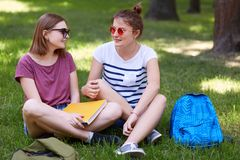 Pretty female youngsters in casual clothes look joyfully at each other, have rest after reading for final exam, sit on green grass royalty free stock photography