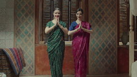 Two women approaching to each other for greeting. Pretty females in colorful sari with bindi, many bracelets and tika decoration coming to each other, turning stock footage